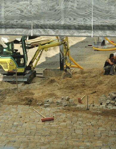 Układanie kostki brukowej granitowej wraz z użyciem sprzętu budowlanego.